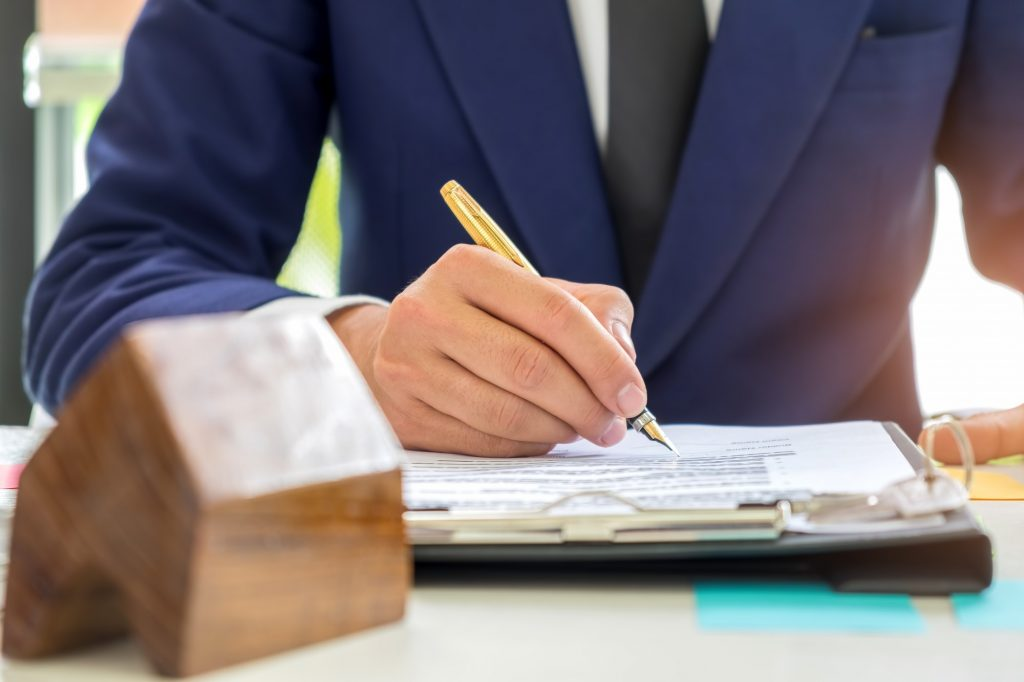 Concept home purchase contract,Businessmen are signing a house p
